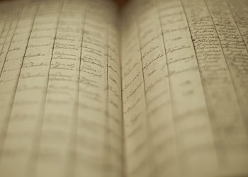 A soft focus of an old book of local records with list of residents' names and information